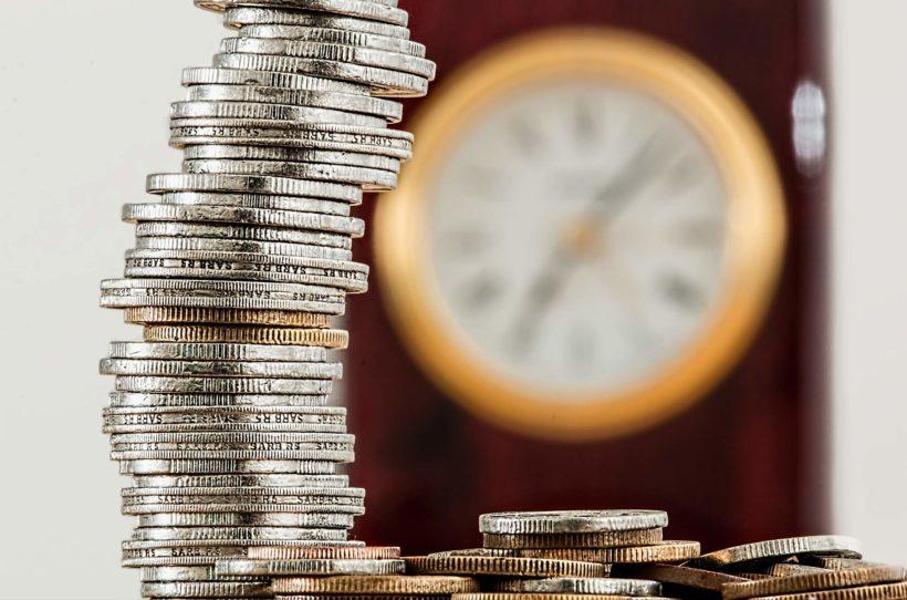 Stapel von 2-Euro Münzen im Vordergrund. Im Hintergrund eine unscharfe Uhr